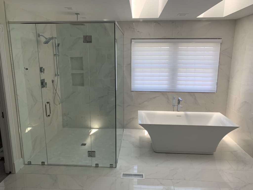 Full view of master bath of bath tub and luxurious glass shower